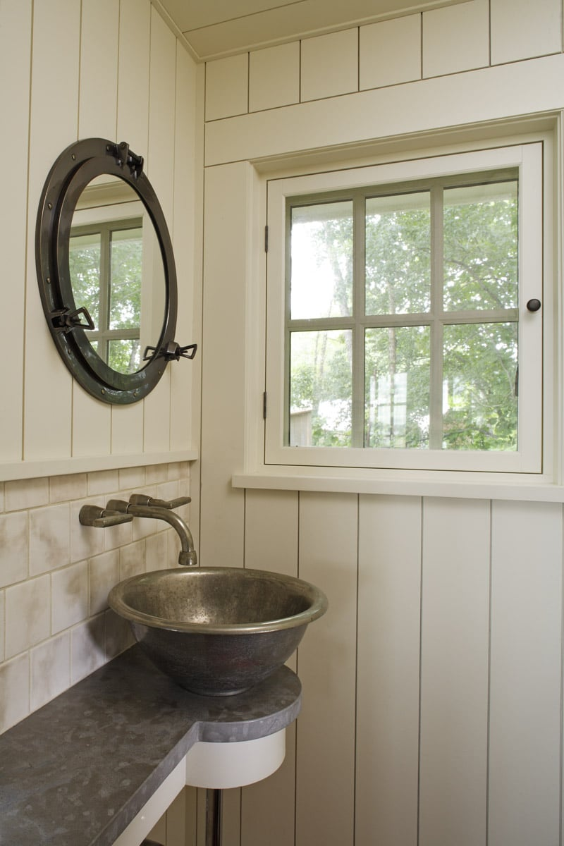 Powder bath with rocky mountain hardware faucet and porthole mirror