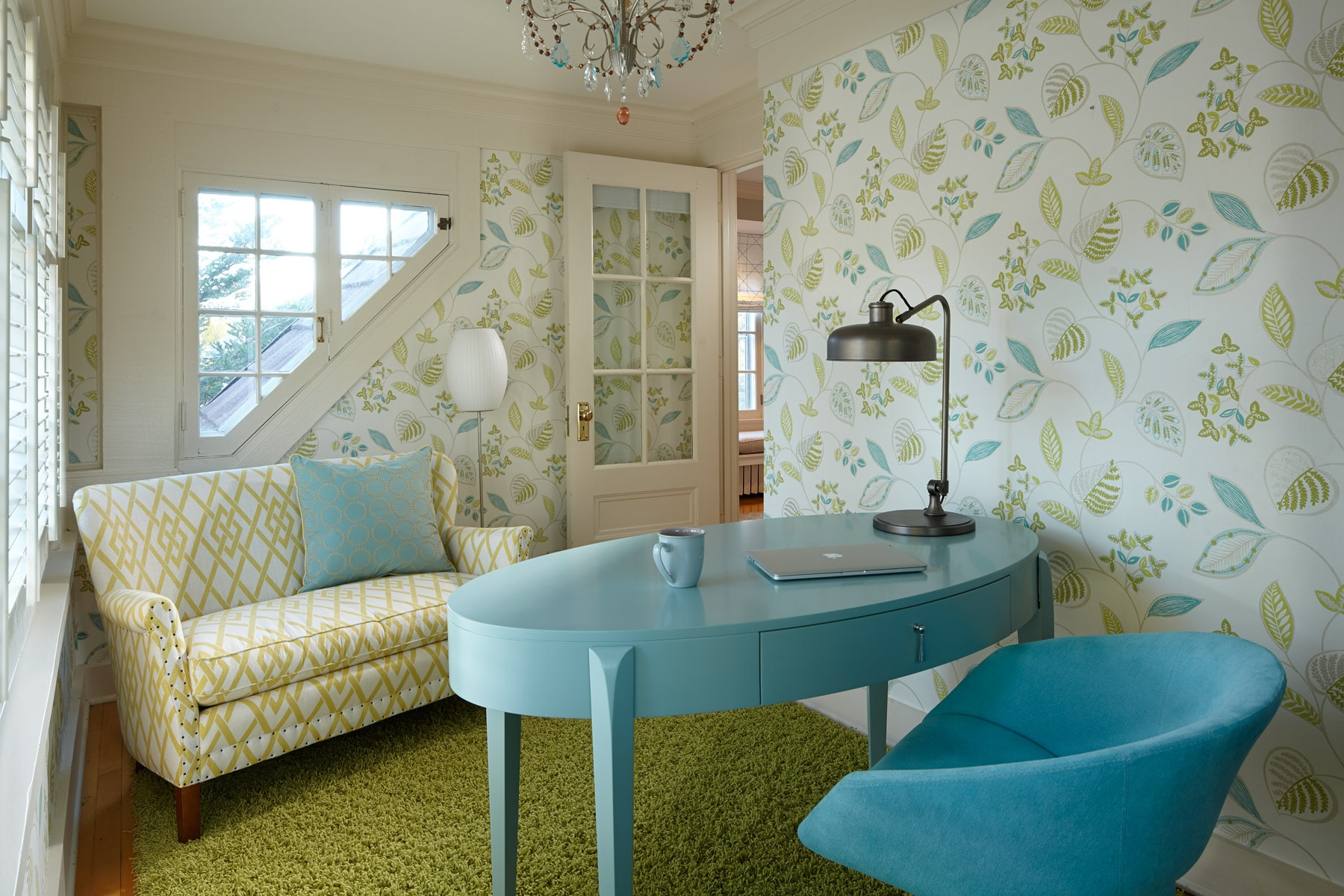 Light blue oval desk and chair in eclectic home office with floral wallpaper