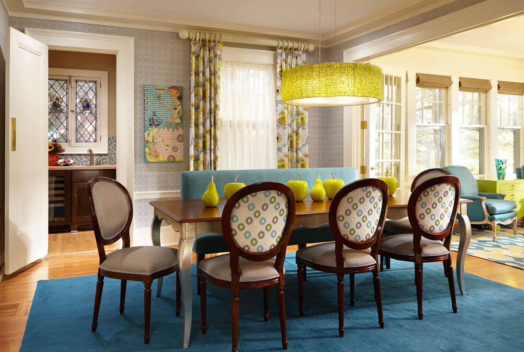 dining room with dark aqua rug, french silver leaf table and banquette seating