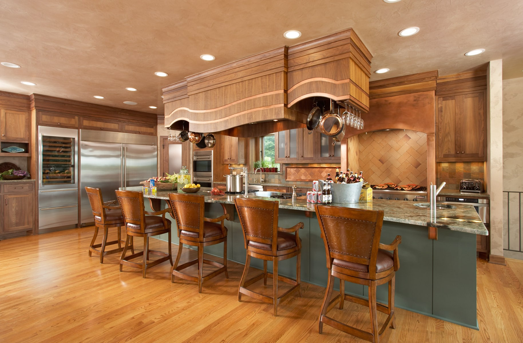 Custom walnut hood over green painted kitchen island