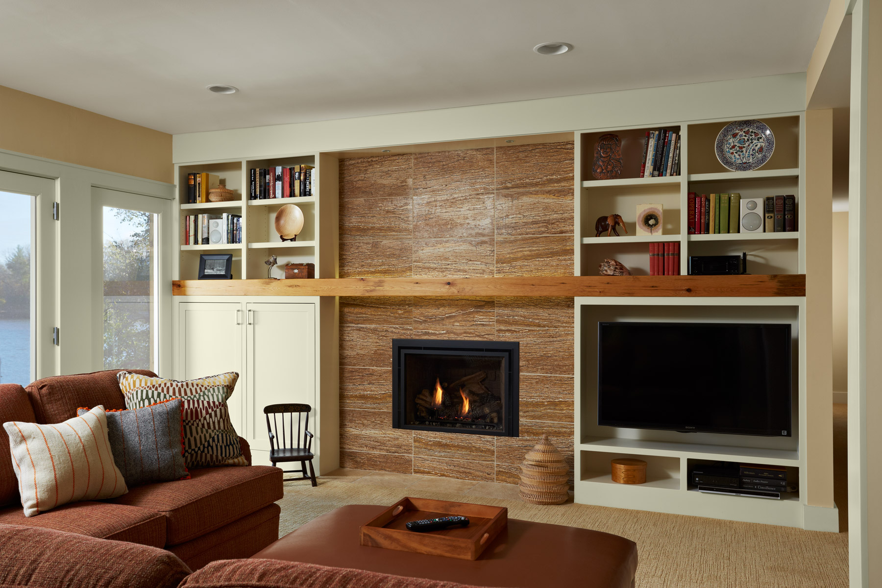 reclaimed wood mantel and stone surround fireplace in renovated lower level rec room