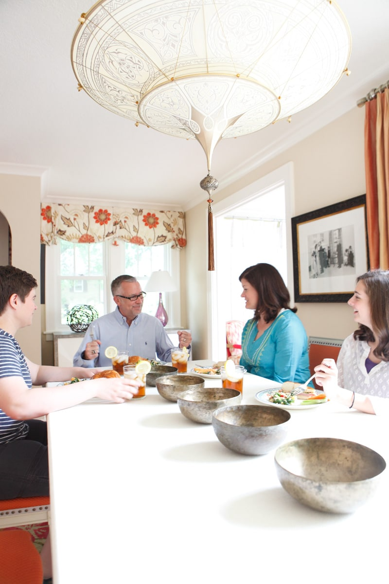 Family at linen-wrapped table in dining room with orange accents