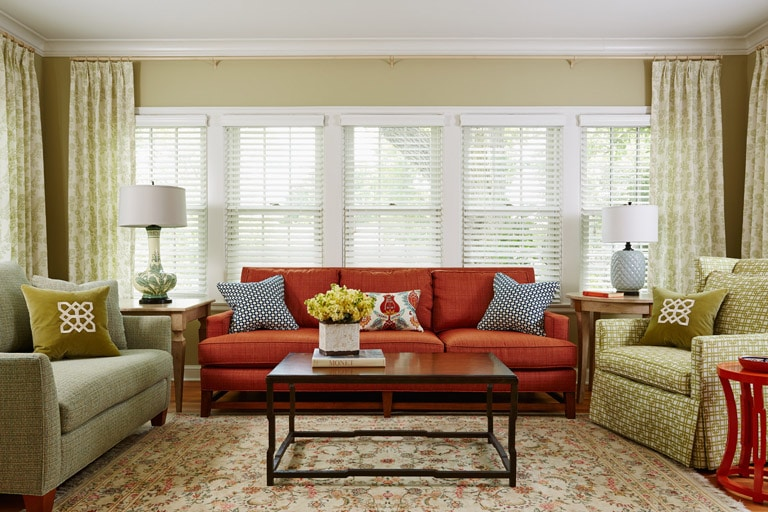 Orange sofa in sunroom with green chairs