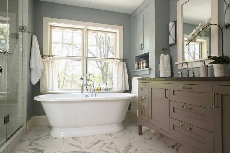 Victoria + Albert soaking tub in beautiful master bath with a blue and neutral color palette