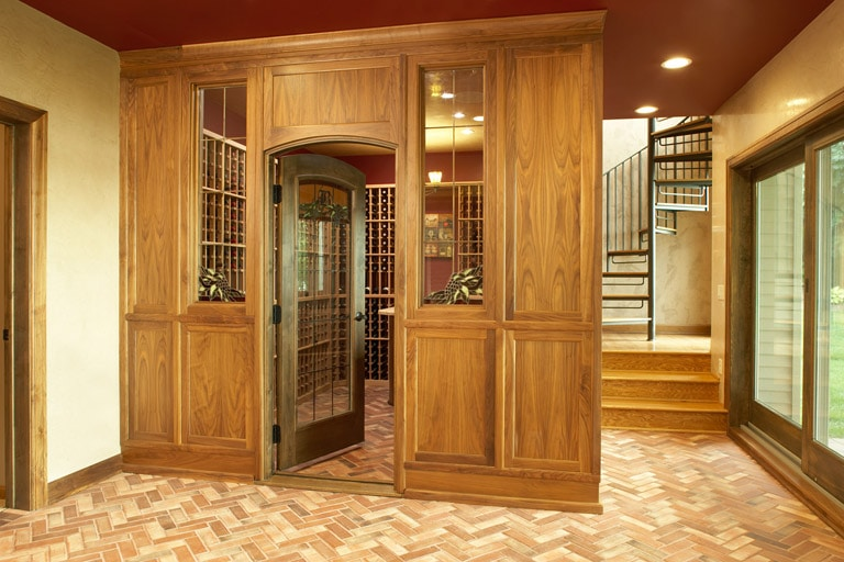 Custom wine cellar with wood paneled walls and brick paver floor