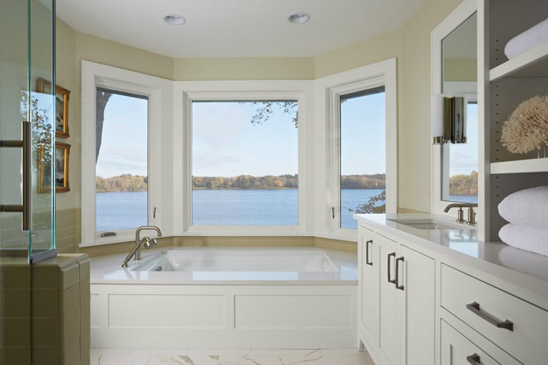 Master bath with lake view, white cabinets and neutral color palette