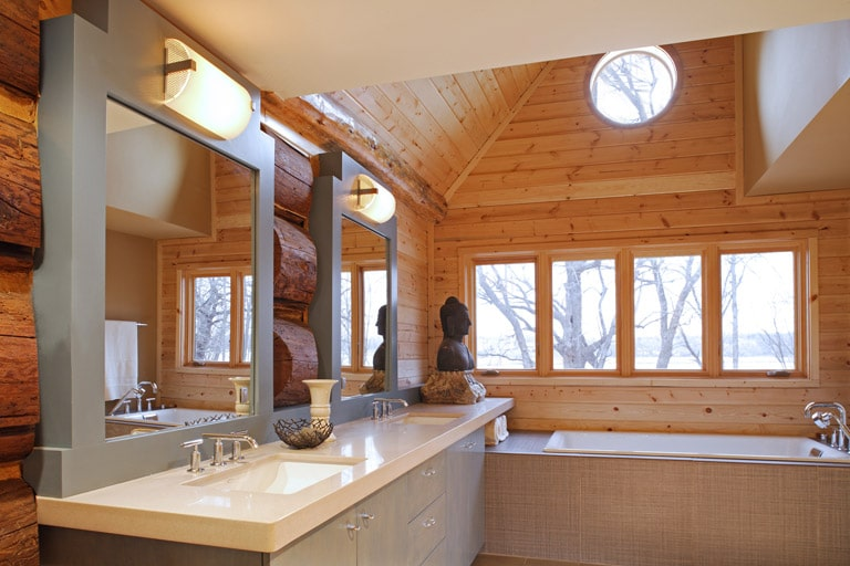Master bathroom in a log home with light blue cabinets and soaking tub