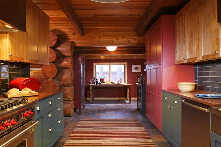 Log Home kitchen with blue-green and red cabinets and luxury appliances