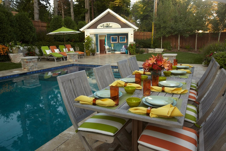 Striped dining chairs at table beside a pool with cabana